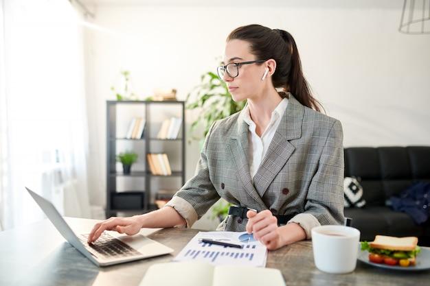 Taille omhoog portret van eigentijdse onderneemster die laptop met behulp van terwijl het werken in bureau, exemplaarruimte