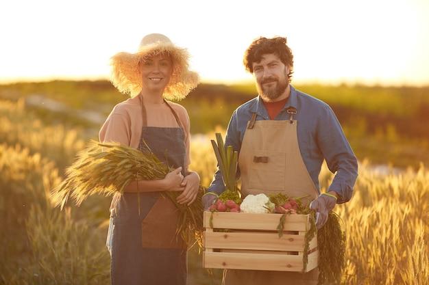 Taille-omhoog portret van glimlachend rijp paar die rijke oogst houden terwijl status in gouden gebied verlicht door zonsonderganglicht, exemplaarruimte