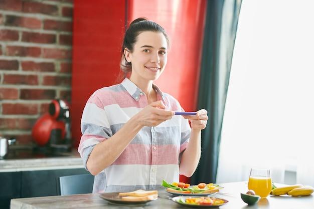 Taille omhoog portret van glimlachende jonge vrouw die foto van voedsel nemen bij ontbijt en camera bekijken