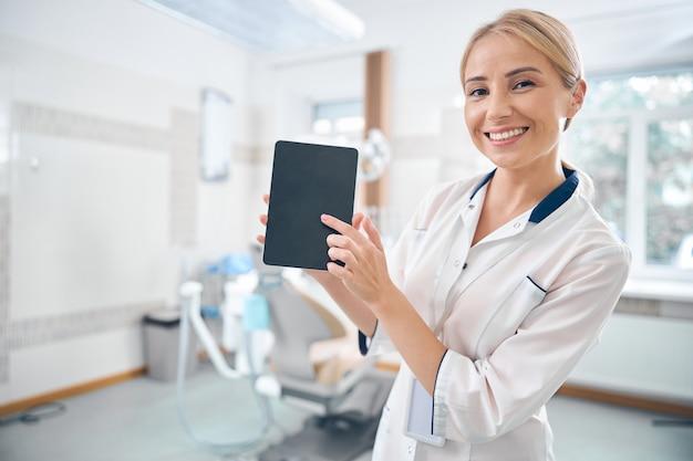 Taille omhoog portret van glimlachende jonge vrouw die in een tandheelkundige kliniek werkt en digitale touchpad vasthoudt