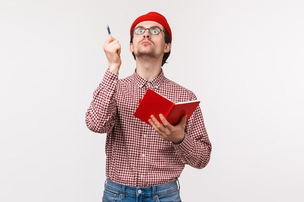 Taille-omhoog portret van grappige mannelijke wetenschapper die aan project werkt, hartstochtelijk opkijkt en pen opheft als perfect idee, notitieboekje vasthoudt, zijn inspirerende gedachten opschrijft, witte muur staat