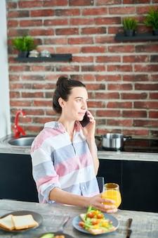 Taille omhoog portret van het moderne jonge vrouw spreken telefonisch thuis tijdens het ontbijt