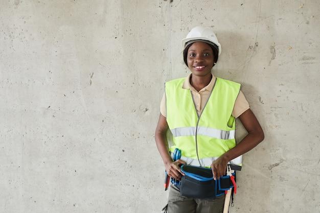 Taille omhoog portret van jonge afro-amerikaanse vrouw die op de bouwplaats werkt en naar de camera kijkt