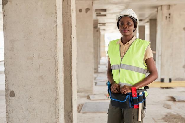 Taille omhoog portret van jonge afro-amerikaanse vrouw die werkt op de bouwplaats en lacht naar de camera...