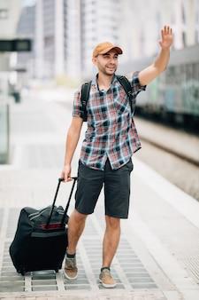 Taille omhoog portret van knappe man die hand opsteekt en wegkijkt en glimlacht op treinstation