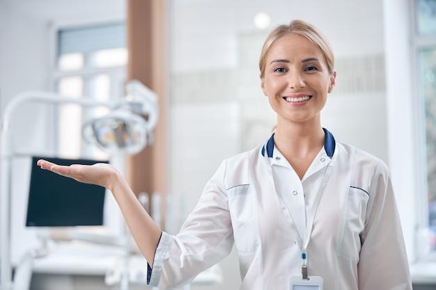 Taille omhoog portret van lachende jonge vrouw in medisch uniform staande in kantoor in de buurt van moderne tandartsstoel