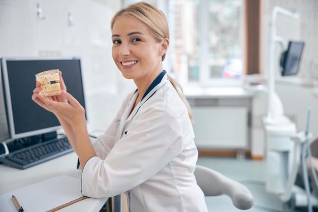 Taille omhoog portret van lachende jonge vrouw in medisch uniform zittend aan de balie in kantoor