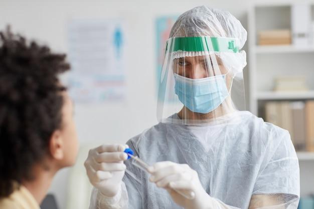 Taille omhoog portret van mannelijke arts die volledige beschermende kleding draagt die covid-uitstrijkje in de kliniek doet, kopieer ruimte