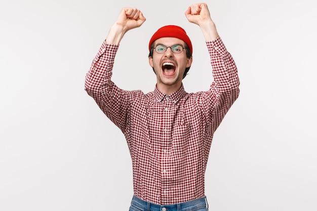 Taille-omhoog portret van opgewonden en opgewonden gelukkig opgeluchte man die prijs wint, prijsuitreiking ontvangt van vreugde en vreugde, handen omhoog steekt in overwinning, zegevierend, groot nieuws vierend