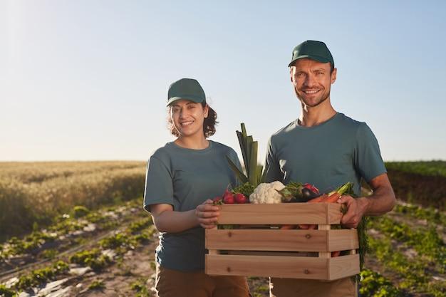 Taille-omhoog portret van twee arbeiders die een doos met groenten houden en naar de camera glimlachen terwijl ze buitenshuis mierenplantage staan, kopieer ruimte