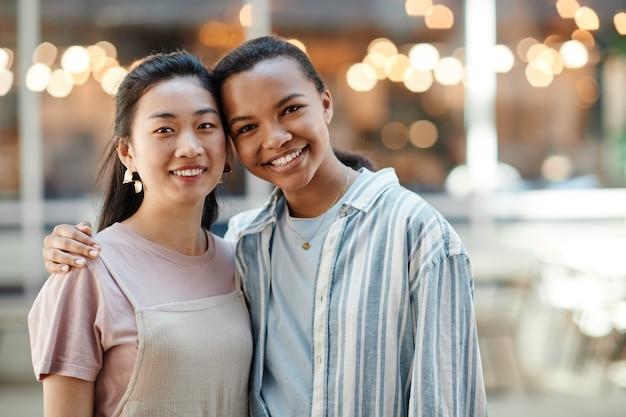 Taille omhoog portret van twee etnische jonge vrouwen die naar de camera kijken terwijl ze buiten in de stad poseren, kopieer ruimte