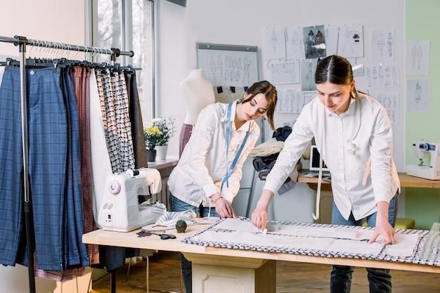 Taille omhoog portret van twee jonge mooie vrouwenkleermakers die met kledingspatronen aan stof werken terwijl het naaien van klassieke broek in atelier, exemplaarruimte