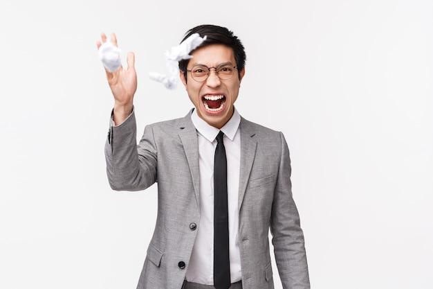 Taille-omhoog portret van verontruste, gestreste en boze jonge aziatische mannelijke manager, kantoormedewerker vernietigt zijn rapport, besluit te stoppen, documenten uit elkaar te halen en ze in de lucht te gooien, schreeuwend verontwaardigd