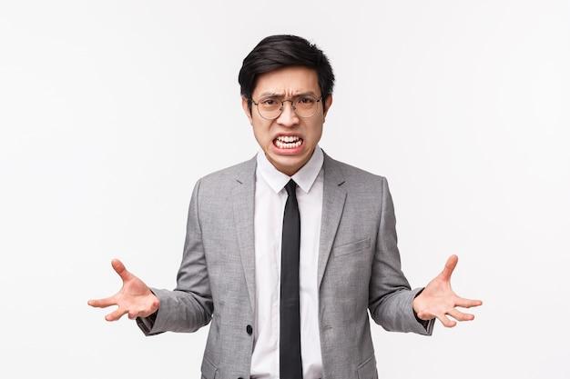 Taille-omhoog portret van verontwaardigde pissige jonge aziatische mannelijke beambte die agressief en gespannen voelt, geduld verliest gebalde vuisten van haat en woede, grimassen gehinderd, kokend van woede