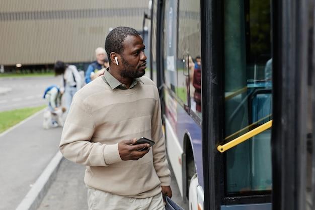 Taille omhoog portret van volwassen afro-amerikaanse man die de bus binnengaat bij de bushalte in de kopieerruimte van de stad