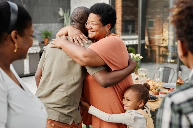 Taille omhoog portret van volwassen afro-amerikaanse vrouw die vriend omhelst tijdens familiebijeenkomst tijdens het diner...