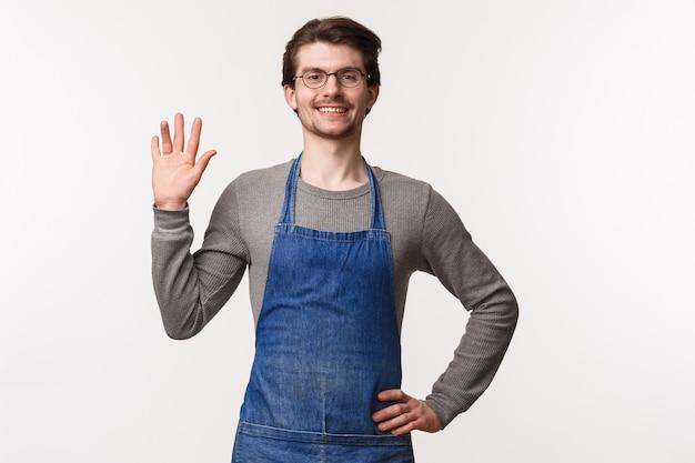 Taille-omhoog portret van vriendelijke uitgaande jonge mannelijke barista in schort, hallo zeggend tegen de klant, mensen begroetend in café als wuivende hand hallo teken, vreugdevol glimlachend, het nemen van koffie of drinken