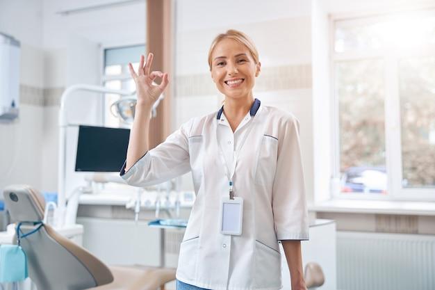 Taille omhoog portret van vrolijke jonge vrouw die in het kantoor in de kliniek staat en een goed gebaar toont showing