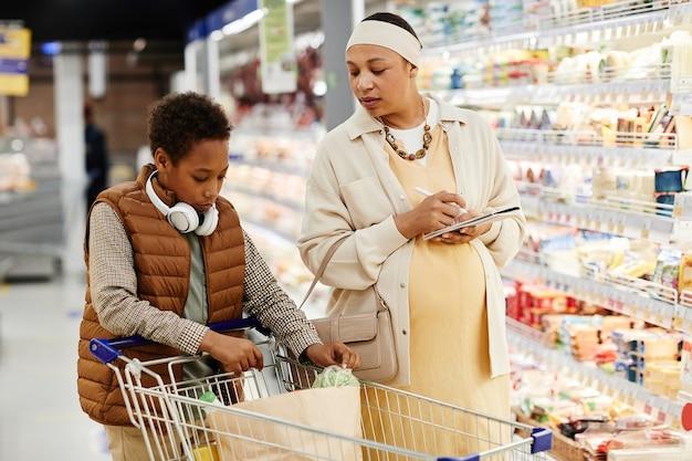 Taille omhoog portret van zwangere afro-amerikaanse vrouw met zoon die boodschappen doet in de supermarkt