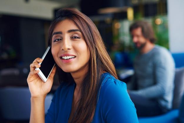Taille omhoog van aziatische vrouw aan de telefoon