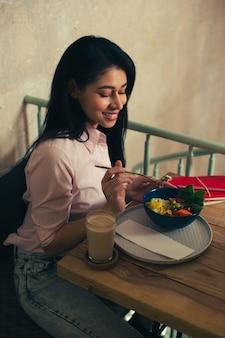 Taille omhoog van een mooie jonge vrouw in jeans en blouse die lacht terwijl ze naar de maaltijd op tafel kijkt en een vork vasthoudt