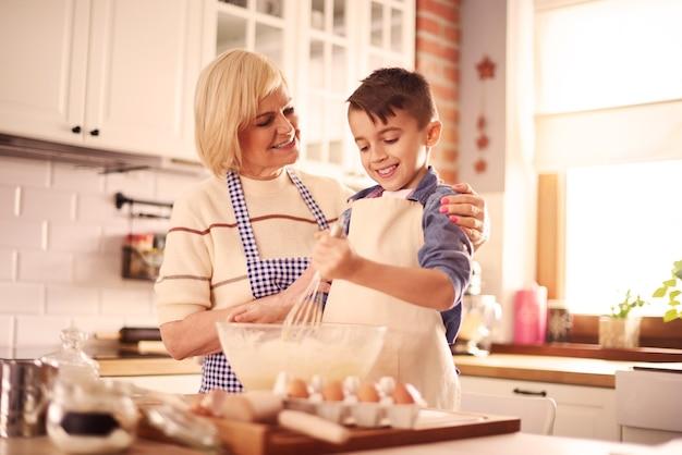Taille omhoog van jongen en grootmoeder in de keuken