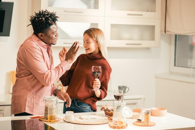 Taille omhoog van positieve jonge dame die voor haar vriend in de keuken staat en een glas wijn vasthoudt terwijl er bloemvlek op de neus zit