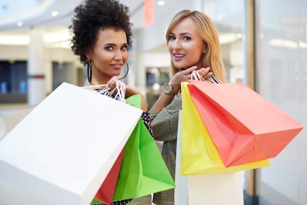 Taille omhoog van twee draaiende vrouwen met boodschappentassen