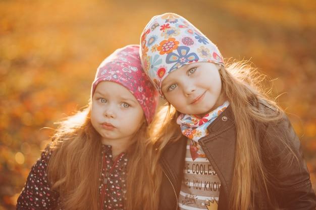 Taille omhoog van twee mooie lachende zusjes die samen in het park staan en knuffelen. jeugd en geluk concept