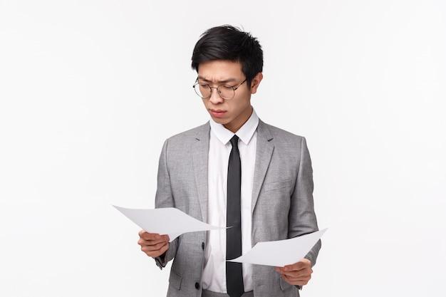 Taille-omhooggaand portret van ernstig ogende drukke aziatische jonge zakenman die gericht en vastbesloten documenten bekijken, belangrijk contract of deal lezen, rapport bestuderen, die in bureau werken