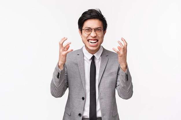 Taille-omhooggaand portret van hatelijke, verontwaardigde agressieve aziatische man in grijs pak, balde handen tot vuisten, grimassen en kijkend met minachting en woede naar, staande op een witte muur