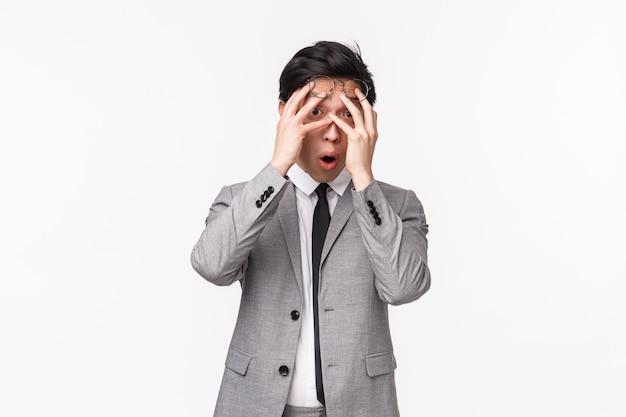 Taille-omhooggaand portret van in verlegenheid gebrachte en geschokte jonge aziatische mannelijke beambte ziet iets onhandigs, hijgend ogen met handen snakkend maar kijkend door vingers als nieuwsgierig