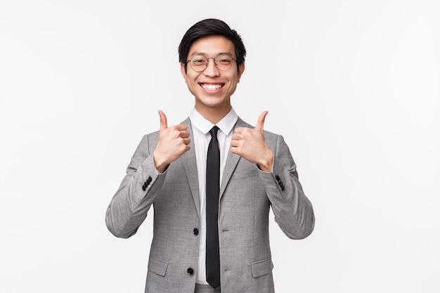 Taille-omhooggaand portret van tevreden, volledig tevreden aziatische jonge mens in grijs kostuum, die duim-omhoog tonen en met goedkeuring glimlachen, zoals ontzagwekkend concept. service aanbevelen, zorg ervoor dat het de beste deal is