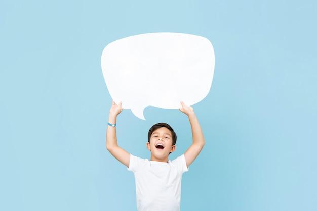 Taille op portret van glimlachende aziatische jongen die een lege witte toespraakbel in lichtblauwe muur steunt