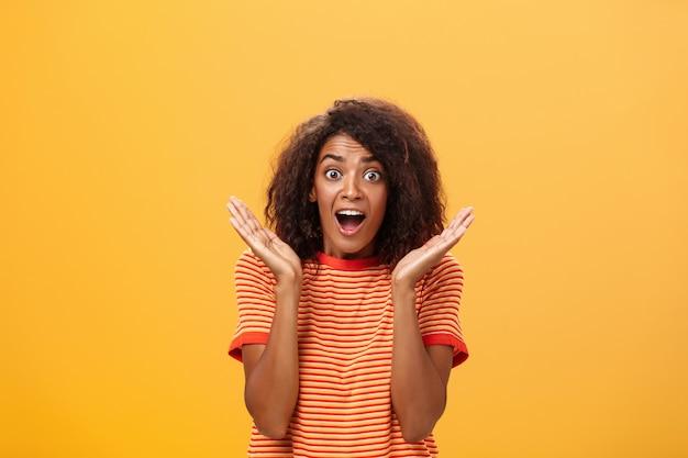 Taille-opname van verbaasde, vrolijke, sociale vrouw met donkere huidskleur met afro-kapsel in gestreept t-shirt gest...