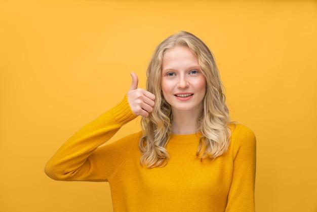 Taille portret met duimen omhoog van mooie jonge glimlachende blonde scandinavische gelukkige vrouw zonder make-up op heldere geeloranje kleur. tiener met fris gezicht en krullend haar
