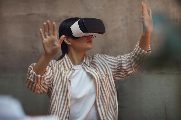 Taille portret van aziatische vrouw vr-uitrusting dragen en gebaren terwijl u geniet van meeslepende ervaring in futuristisch interieur