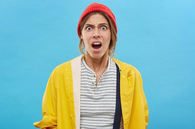 Taille portret van geschokt of gefrustreerd modieuze jonge vrouw, met verbaasde en verbaasde uitdrukking op haar gezicht. grappig meisje mond openen in shock en verbazing