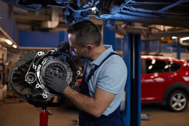 Taille portret van gespierde automonteur inspecteren versnellingsbak in auto reparatiewerkplaats, kopie ruimte
