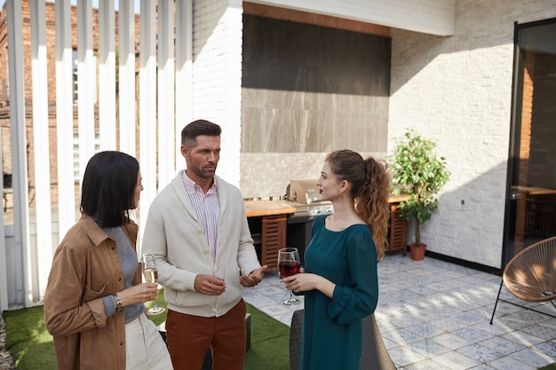 Taille portret van hedendaagse volwassen mensen chatten terwijl staande op terras tijdens feest,