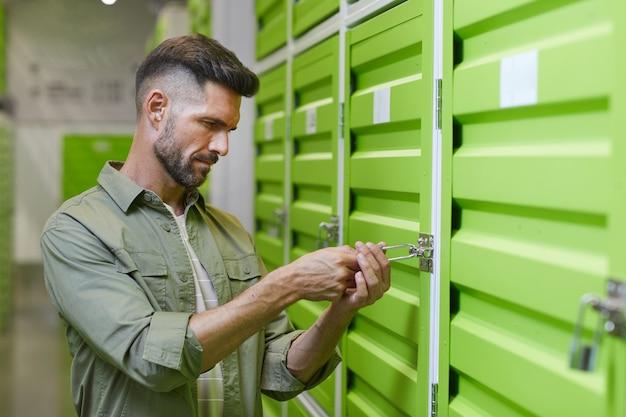 Taille portret van knappe bebaarde man opening hangslot op deur van self storage unit, kopie ruimte