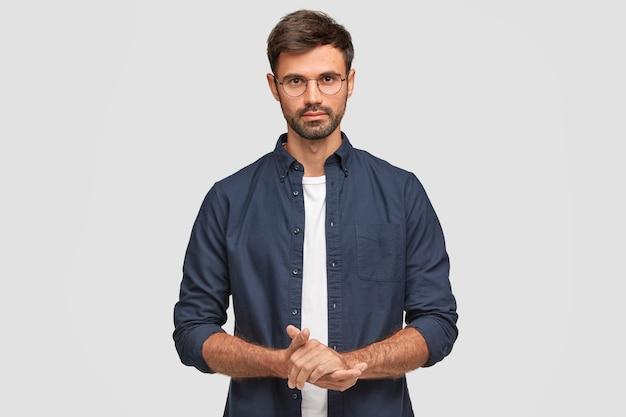 Taille portret van knappe ernstige ongeschoren man houdt de handen bij elkaar, gekleed in een donkerblauw shirt, heeft een gesprek met de gesprekspartner, staat tegen een witte muur. zelfverzekerde man freelancer