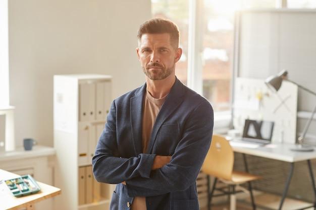 Taille portret van knappe volwassen zakenman terwijl staande met armen gekruist in kantoor verlicht door zonlicht,
