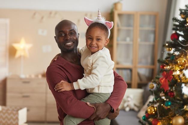 Taille portret van liefdevolle afro-amerikaanse vader schattig klein meisje te houden en glimlachend in de camera terwijl poseren door de kerstboom thuis in gezellig interieur.