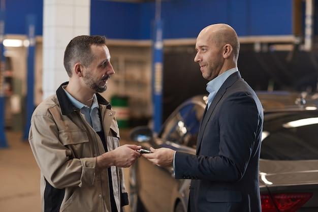 Taille portret van monteur sleutels geven volwassen zakenman na controle van luxeauto bij jaarlijkse inspectie, kopie ruimte