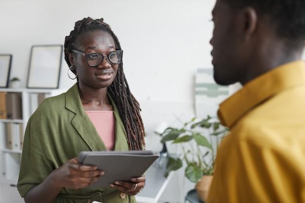 Taille portret van stijlvolle afro-amerikaanse vrouw spreken met mannelijke collega tijdens de bespreking van project in kantoor