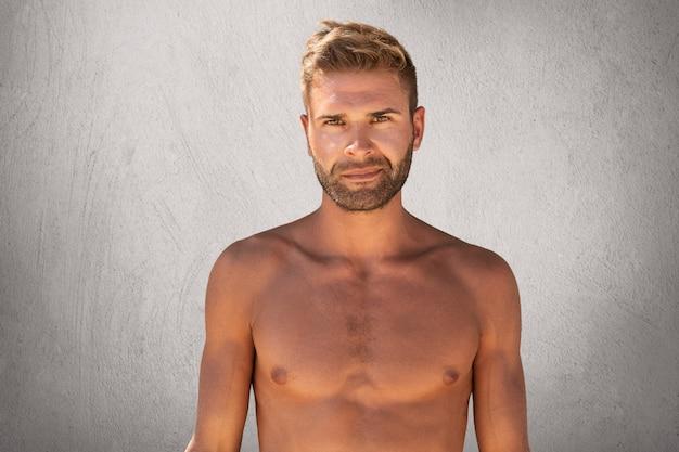 Taille portret van topless ongeschoren jonge man met een sterk lichaam staande tegen een grijze achtergrond