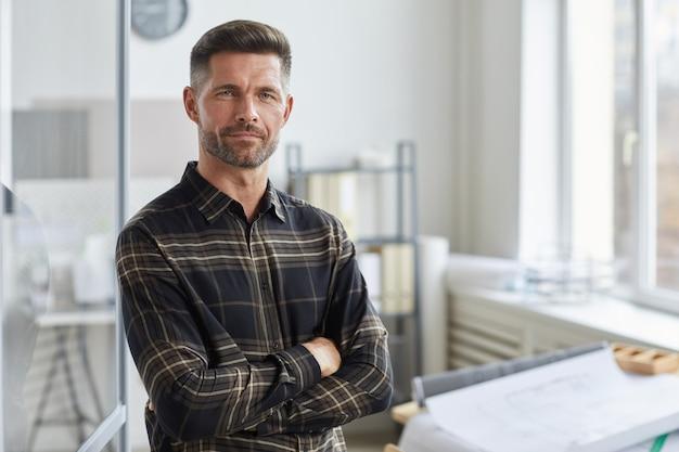 Taille portret van zelfverzekerde bebaarde architect staand met armen gekruist door tekentafel in kantoor,