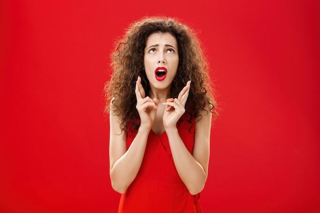 Taille shot van onrustige en bezorgde onzekere aantrekkelijke rijke dame in rode jurk fronsend klagend...