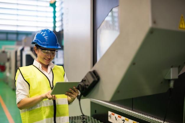 Taille-technicus of inspecteur-vrouw met tabletcontrolestatus of onderhoudsmachine door bedrijfstoepassing in de fabriek.